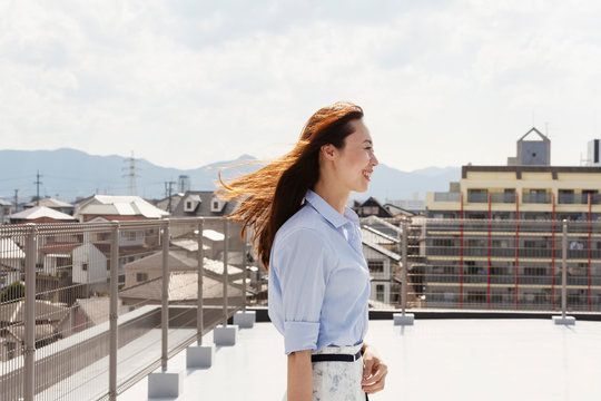 Smiling Japanese woman standing on a rooftop in an urban setting.