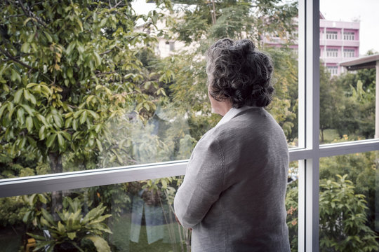 back view, Portrait of elderly Asian senior woman with grey hair looking out window for thinking seriously, lifestyle concept