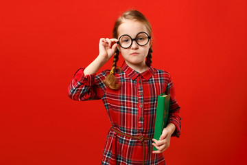 Funny child in glasses and with a book on a red background. Portrait of a serious smart little girl