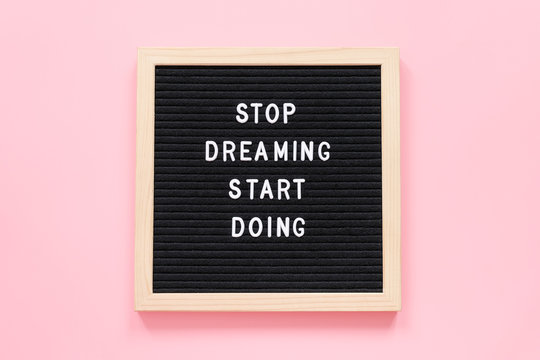 Stop Dreaming Start Doing. Motivational quote on letterboard on pink background. Top view Flat lay Concept inspirational quote of the day