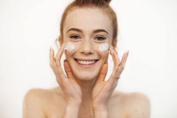 Portrait of a charming young woman looking at camera laughing while playing with both hands cream on her cheeks.