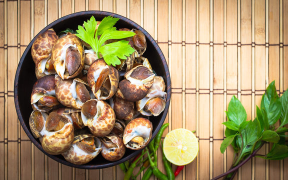 Boiled Babylonia areolata or shellfish on wooden bowl with lemon and chilli on table.Sea food. Topview