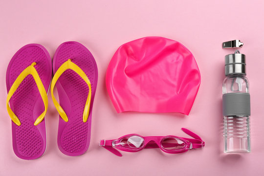 Flat lay composition with swimming accessories on pink background