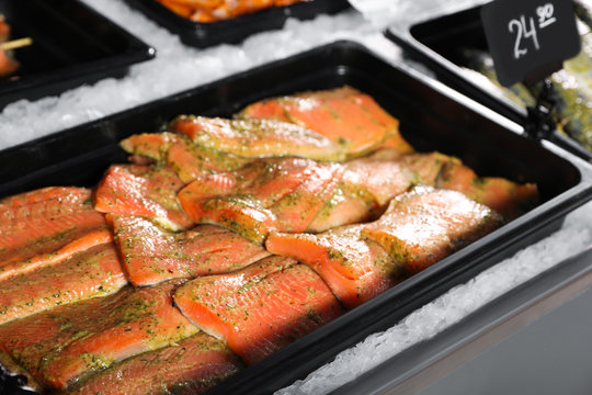 Fresh marinated fish in container on display, closeup
