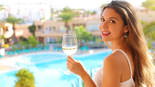 Smiling young woman drinking white wine on outdoor resort terrace. Happy beautiful woman in white dress on summer travel vacation looking at camera.