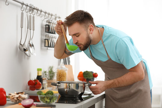 Young man cooking delicious soup in kitchen
