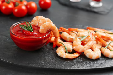Delicious shrimp cocktail with tomato sauce served on black table
