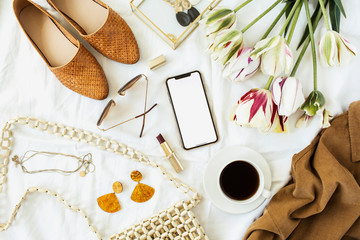 Women's fashion / beauty blog home office desk. Blank screen mobile smart phone, tulip flowers bouquet, clothes and accessories. Flat lay, top view copy space mockup background.