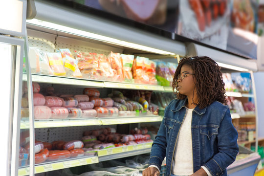 Pensive African American woman wheeling shopping cart in grocery store, looking at sausages and ham. Buyer shopping in supermarket. Food shop concept