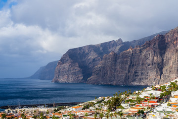Spain, Tenerife, Beautiful aerial view above houses of famous coastal city next to giant cliffs called los gigantes with rain clouds