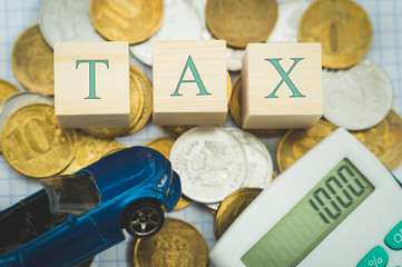 auto tax, blue toy car coin calculator, word tax on on wooden cubes
