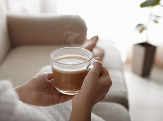 Woman with cup of hot drink on sofa at home in morning, closeup Fototapete