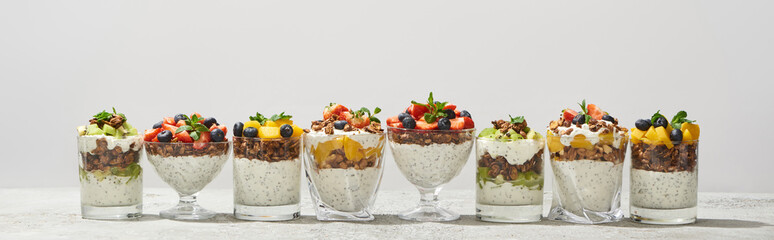 delicious granola in glasses with fruits and berries isolated on white, panoramic shot