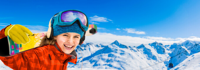 Wall Mural - Young girl with ski in winter season, view from ski run at mountains and Val Thorens resort in sunny day in France, Alps.