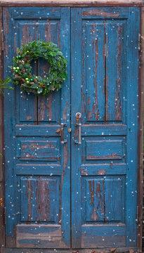 Christmas handmade wreath with green balls, cinnamon sticks, cones on blue wooden rustic door