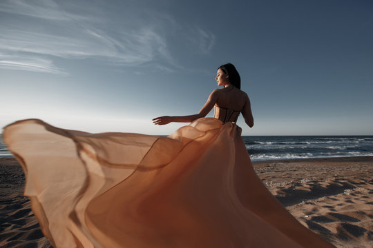 Girl in a light dress on the beach at sunrise.beautiful women in a light pink dress walking along the beach at dawn.Good morning and relaxation.Young beautiful girl standing on a sandy beach in a ligh