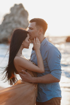 Couple in love at dawn by the sea. Honeymoon trip. Man and woman traveling. Happy couple by the sea view from the back. Man and woman holding hands. Couple in love on vacation. Follow me. Couple on a