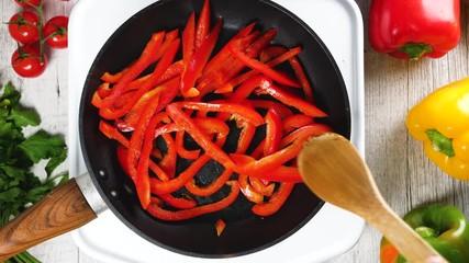 Fotobehang - red bell pepper in cooking pan, top view, 4K