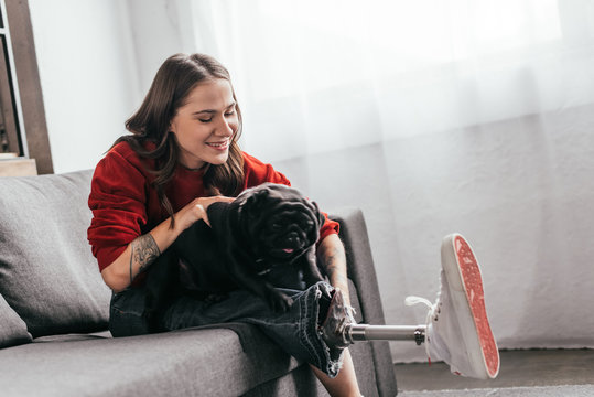 Smiling woman with prosthetic leg playing with pug on sofa