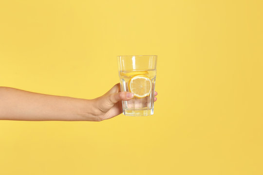Young woman holding glass of lemon water on yellow background, closeup