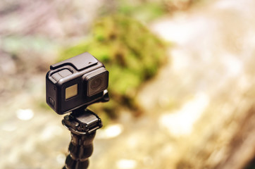 Action camera on a flexible tripod on green forest background