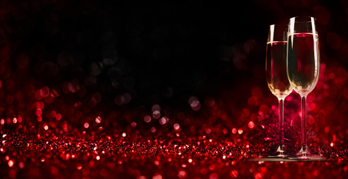 Two champagne glasses on sparkling red bokeh background. Valentine's day dinner invitation. Christmas and new year holiday party.