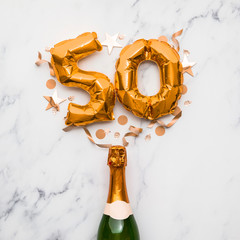 Champagne bottle with gold number 50 balloon. Minimal party anniversary concept