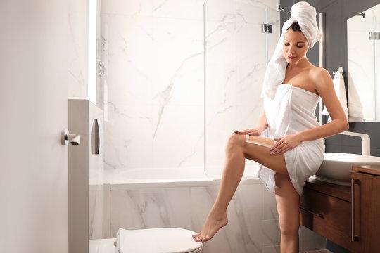 Young woman waxing her legs in bathroom. Epilation procedure