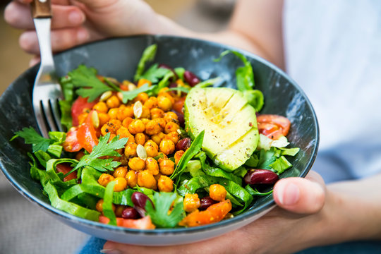 Clean eating, vegan healthy salad bowl closeup , woman holding salad bowl, plant based healthy diet with greens, chickpeas and vegetables