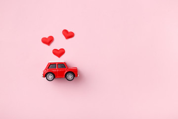 Poster Vintage voitures Red retro toy red car with red bow for Valentine's day on pink background with heart confetti. Top view, flat lay