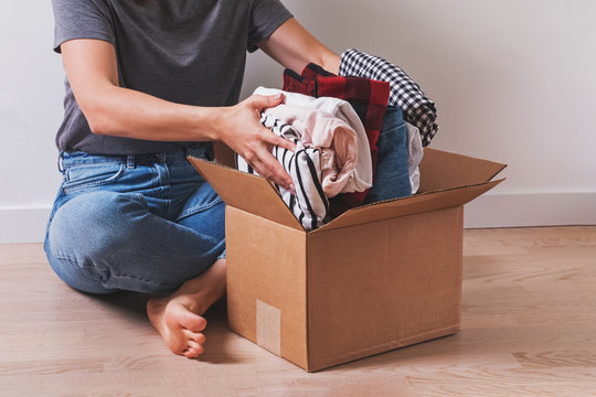 Unrecognizable woman putting clothes in cardboard box while sitting on the floor.