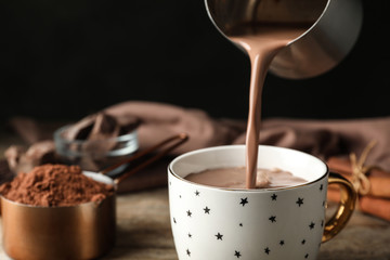 Papiers peints Chocolat Pouring hot cocoa drink into cup on wooden table