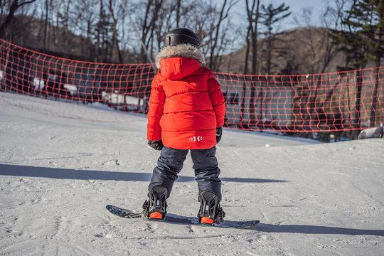 Little cute boy snowboarding. Activities for children in winter. Children's winter sport. Lifestyle