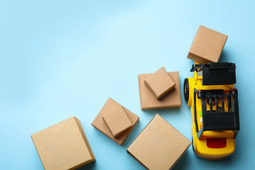 Top view of toy forklift with boxes on blue background, space for text. Logistics and wholesale concept