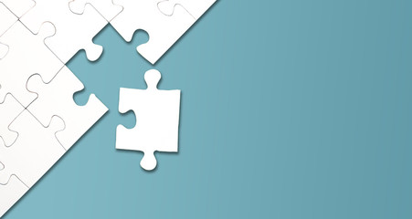 top view of jigsaw puzzle with one piece left on blue background, completing a task or solving a problem concept