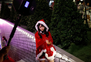 A woman poses for a photo with Christmas lights near a shopping center in Bangkok