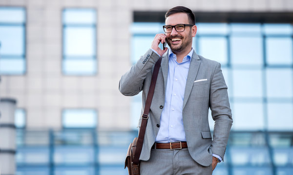 Businessman talking with mobile phone in front of the corporation. Business, education, lifestyle concept