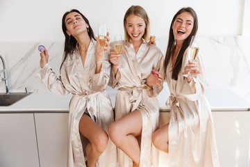 Cheerful young girls women drinking champagne.