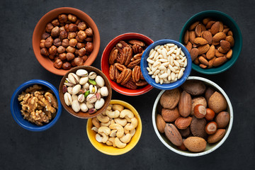 Variety of different types of nuts - almonds, pine nuts, pastachio, cashew, walnuts, pecan and hazelnuts- in bowls. Overhead view