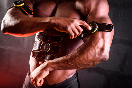 African american male bodybuilder uses electronic myostimulator to train biceps hands and abdominal muscles on a black background
