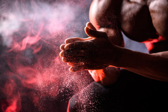 Black bodybuilder uses hand magnesia. A man sits on a black background with red smoke