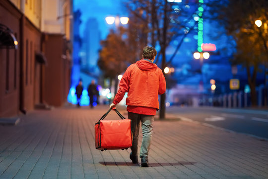 Young deliveryboy walking with red thermal bag on night city street. Man of delivery service in hurry to deliver an order. Delivery service goes to give the order quickly to the client at night
