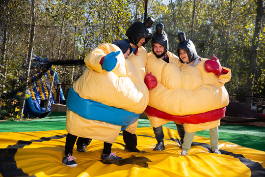 Friends posing in inflatable sumo suits