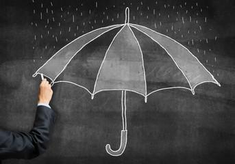 Businessman hand with chalk draws umbrella sketch