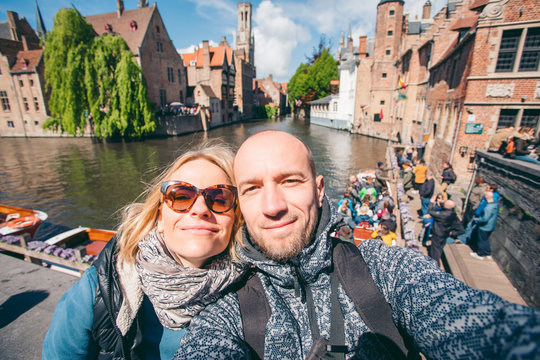 Young couple takes selfie pictures on the main street of Bruges, Belgium.