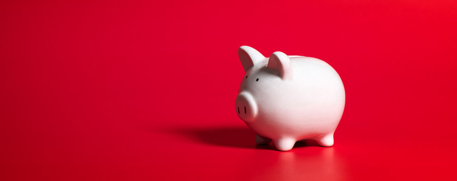 Composition with piggy bank isolated on red background.