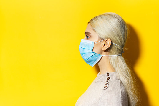 Studio profile portrait of young blonde girl, wearing flu medical mask on yellow background with copy space.