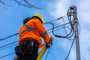 A telecoms operative is seen working from a ladder on a utility pole, wearing high visibility personal protective clothing, high viz PPE, and hard hat