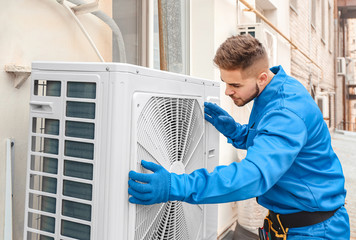 Male technician installing outdoor unit of air conditioner Fotobehang