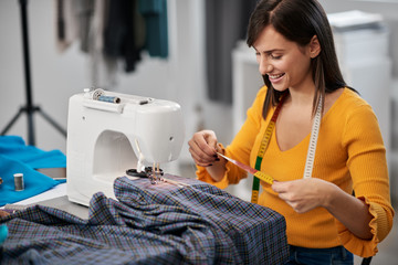 Focused charming caucasian fashion designer sitting in her studio and measuring textile for beautiful evening dress.